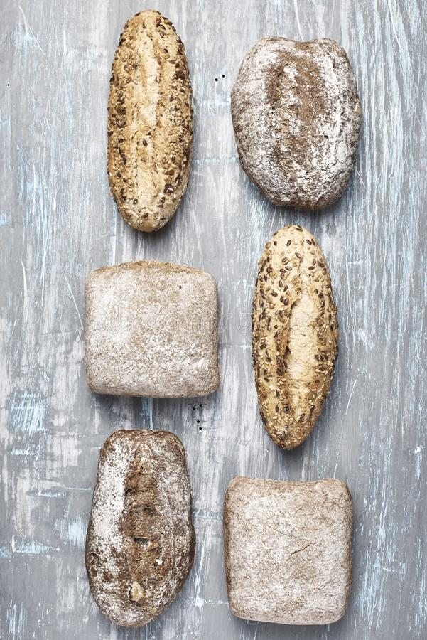 Organized arrangement of loaves. From above shot of shabby surface with various bread loaves arranged in lines royalty free stock photos