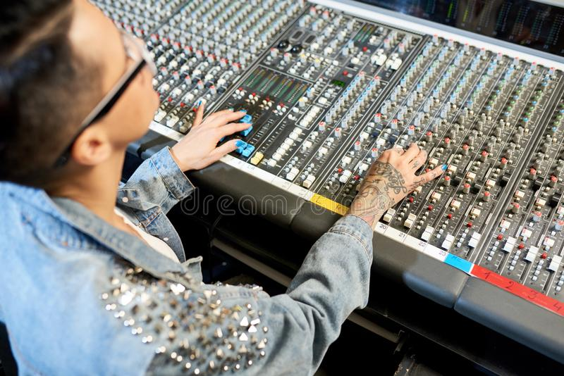 Tattooed woman working on control console stock photo
