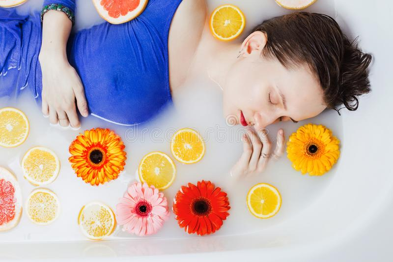 Woman in blue dress lying in bathtub filled with white water royalty free stock images