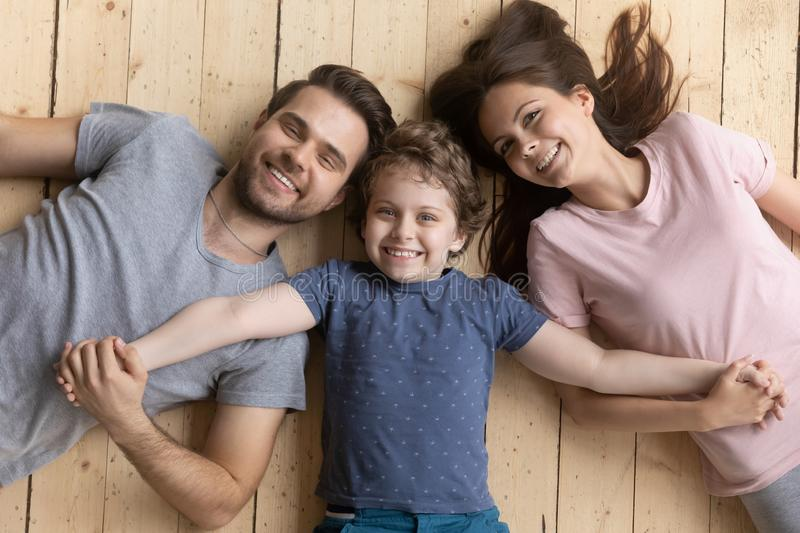 Above view happy adopted little boy holding hands of parents. stock photos
