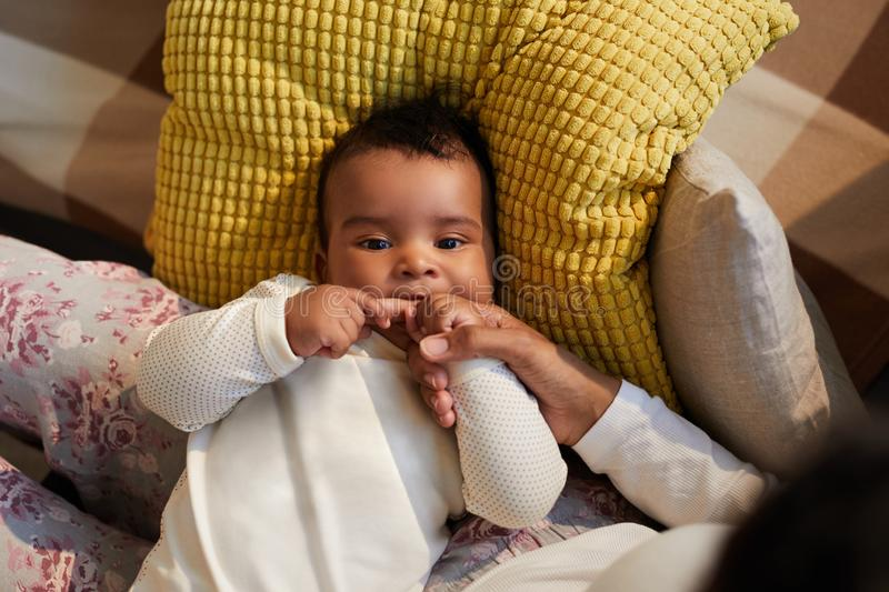 African baby being teething. Above view of adorable African baby boy in cute sweater lying on mothers legs and biting her finger because of teething stock photo