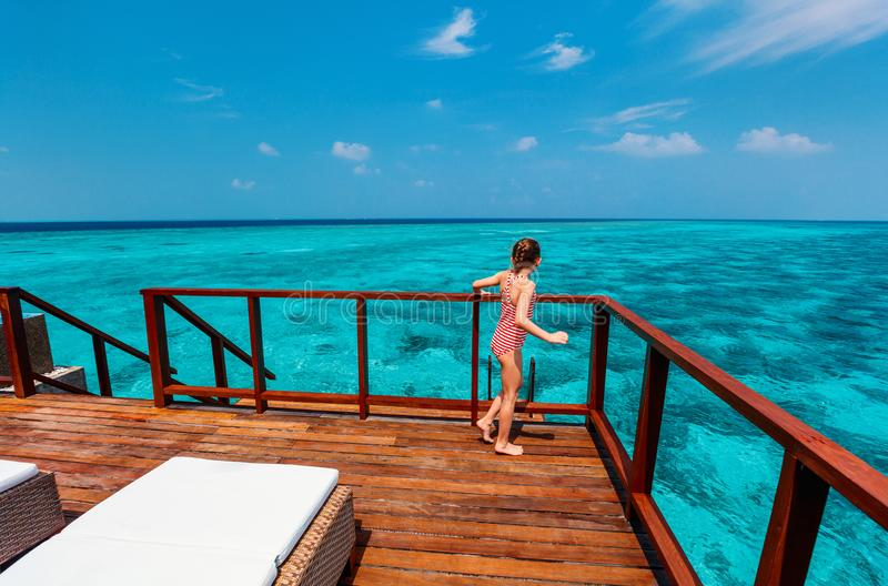 Adorable little girl on vacation. Above view of adorable little girl at luxury overwater villa near tropical ocean in Maldives royalty free stock photos