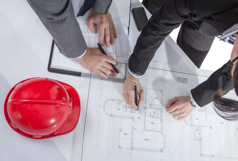 Above view of architects hands revising a house project stock photos
