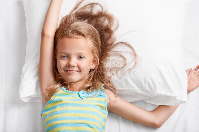 Above view of attractive light haired small child, has blue eyes, stretches in bed, lies on white pillow, dressed in colourful str royalty free stock photo