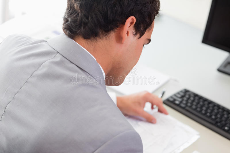 Above view of businessman doing paper work. Above view of young businessman doing paper work stock image