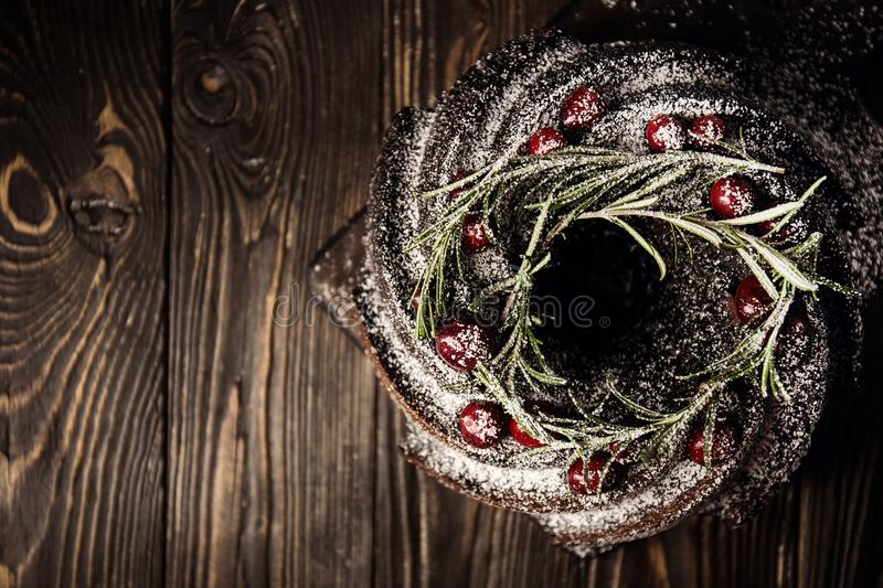 Delicious chocolate pie decorated for Christmas. From above view of chocolate caked topped with sugar powder and berries for delicious holiday stock photo