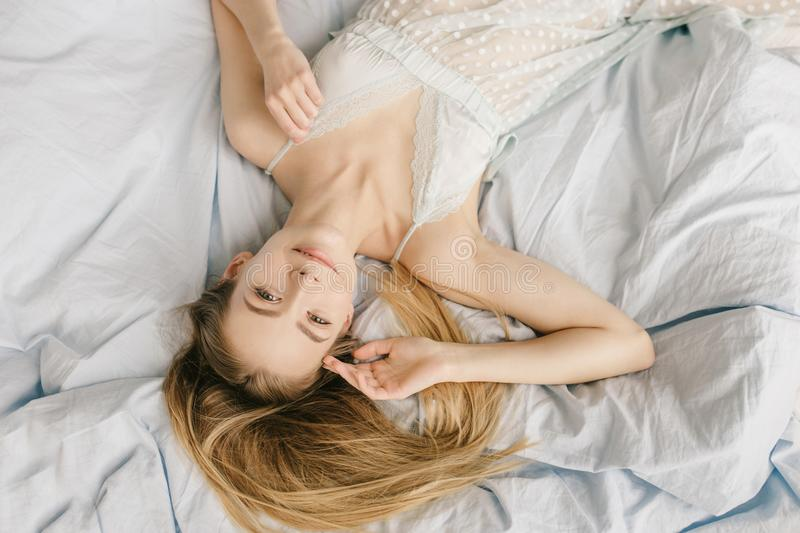 Above view of a cute smilling girl in light pajamas is resting in warm cozy bed. Light blue bed sheets royalty free stock images