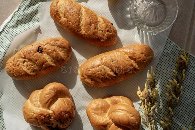 Braided bread loaves and small bread loaves. Above view of flat lay food still life with braided bread loaves and individual bread loaves stock images