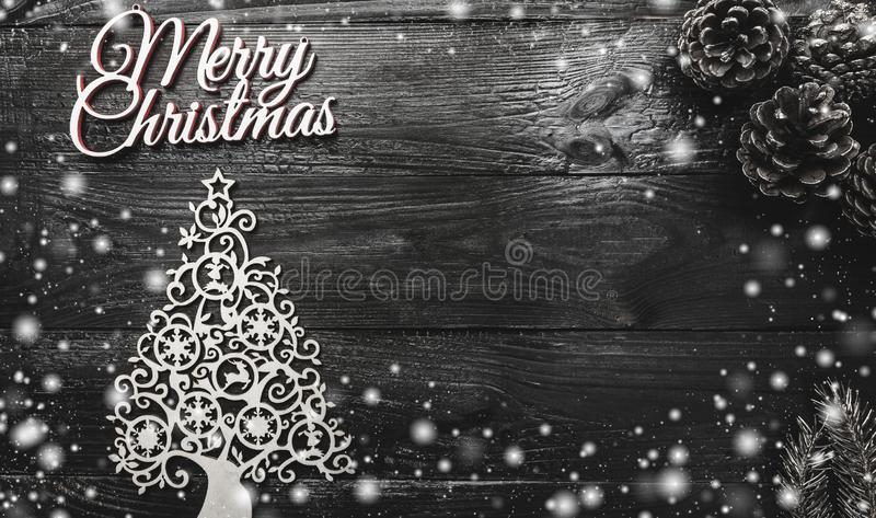 Above view of handmade evergreen tree toy, golden pines and Merry Christmas inscription on black wooden background stock photography