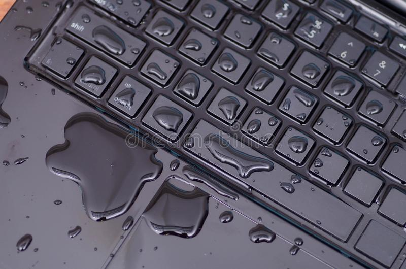 Above view of laptop with water drop damage liquid wet and spill on keyboard, accident concept royalty free stock photography