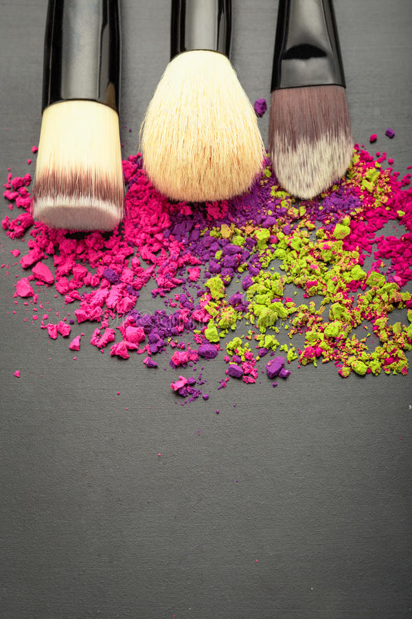 Above view on make-up brushes with colorful eyeshadow. Above view on make-up brushes with colorful make-up eyeshadow on black texture with copy space stock images