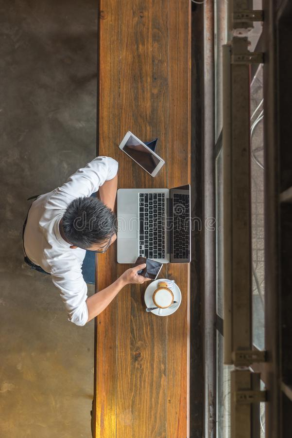 Above view of man using laptop and other hi-tech devices. Such as smartphone, tablet, laptop royalty free stock photography