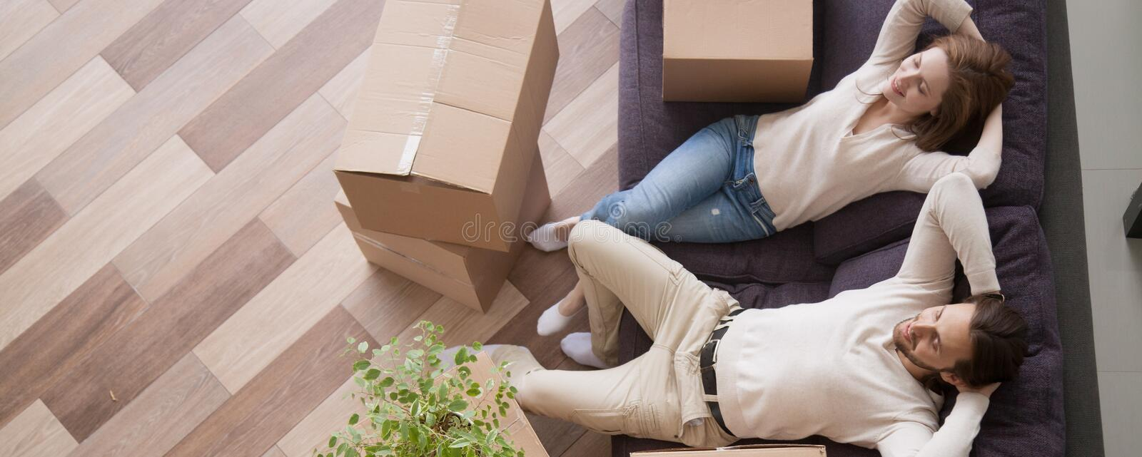 Above view married couple resting on couch at moving day. Horizontal above concept photo married couple at moving day rest relax on couch cardboard boxes on royalty free stock photo