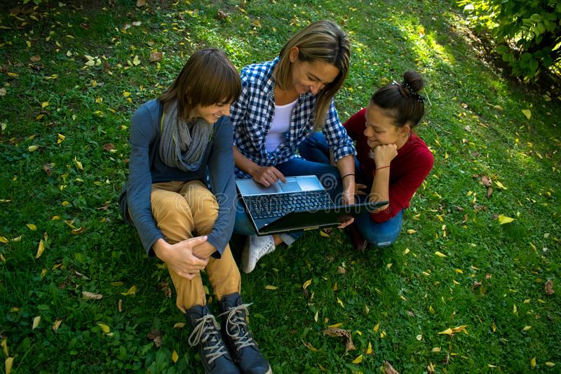 Above view of happy mother and children using computer in the park. royalty free stock photo