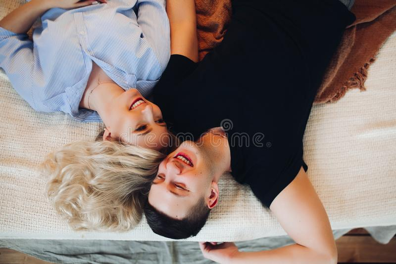 Above view of positivity couple laying together on back and happy smiling. stock images