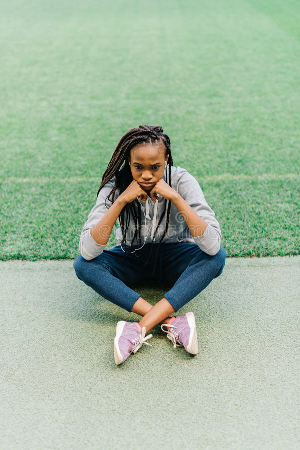 Above view of the sad afro-american teenager sitting on the grass and leaning on the hands. royalty free stock photography
