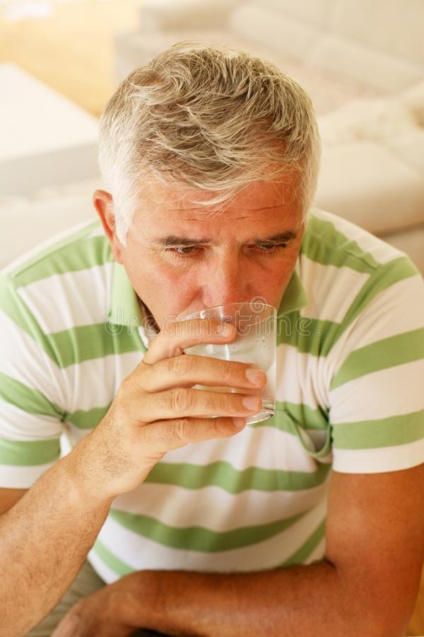 Above view of senior man drinking water. Above view of senior man drinking water at home stock image