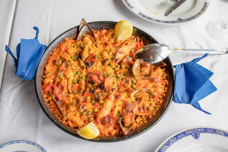 Above view of typical Spanish paella with seafood mussel, prawn, lobster, squid, clam, rice and lemon ready to serve on white. Tablecloth of restaurant royalty free stock image