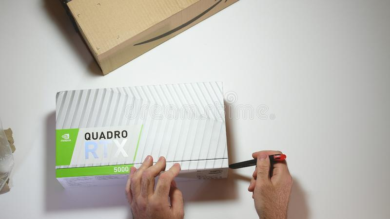 Above view unboxing of Nvidia Quadro RTX 5000 GPU cutter. Paris, France - Feb 20, 2019: View from above POV man cutting unboxing latest Nvidia Quadro RTX 5000 royalty free stock images