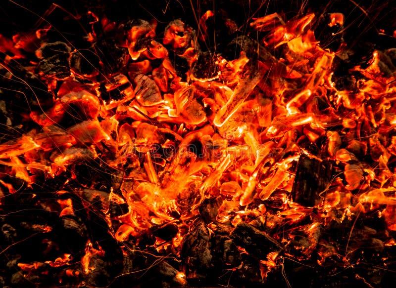 abrégez le fond charbons de bois brûlants avec des étincelles image libre de droits