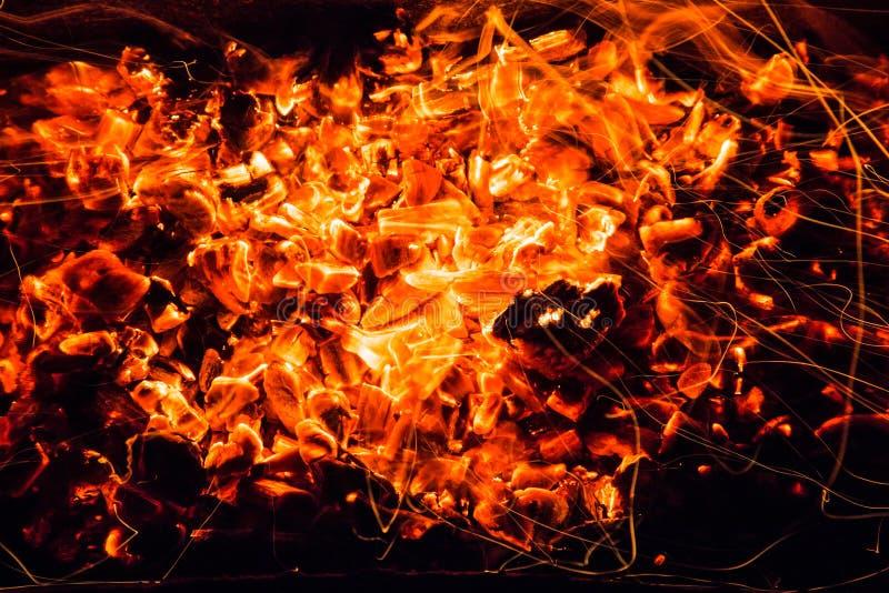 abrégez le fond charbons de bois brûlants avec des étincelles images stock