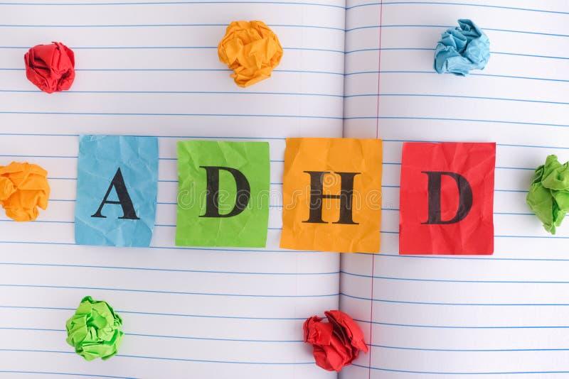 Abréviation ADHD sur la feuille de carnet avec quelques boules de papier chiffonnées colorées autour de elle photos libres de droits