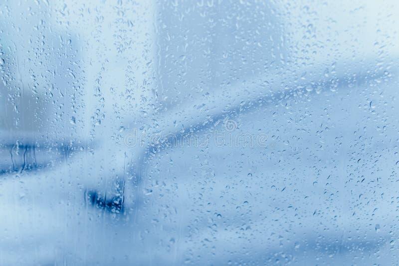 Abr?g? sur le trafic en hiver Le trafic vu de l'int?rieur d'une voiture Baisses de l'eau sur des lumi?res de queue de pare-brise  photos libres de droits