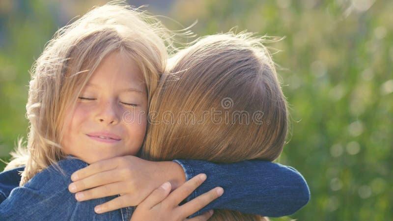 Abraçando a mãe e a filha no verão imagens de stock
