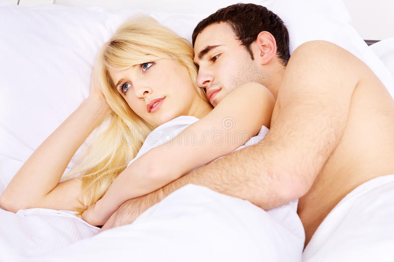 Abraçando a na cama foto de stock royalty free