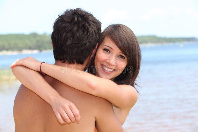 Abraçando o noivo na praia fotos de stock