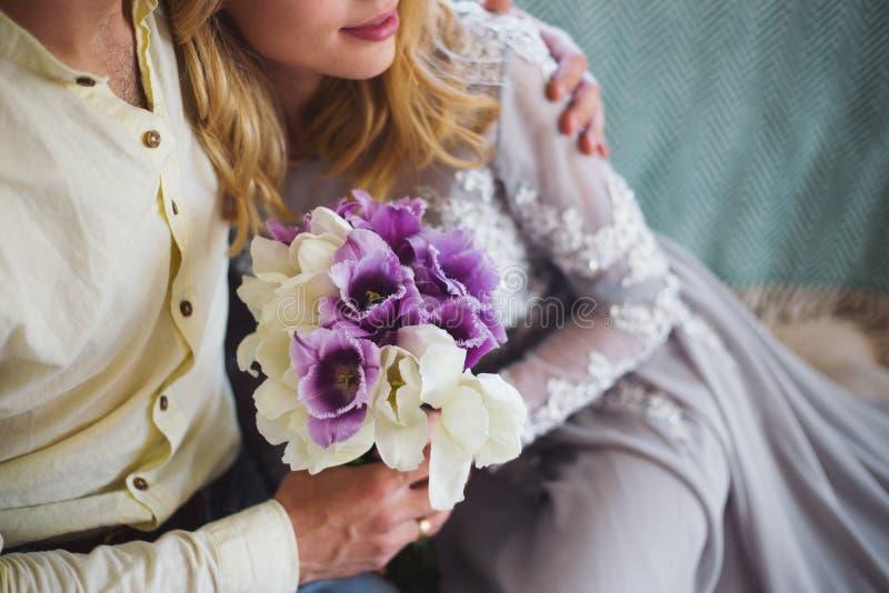 Abraçando os pares novos românticos bonitos que guardam o ramalhete macio da mola de tulipas roxas e brancas fotografia de stock