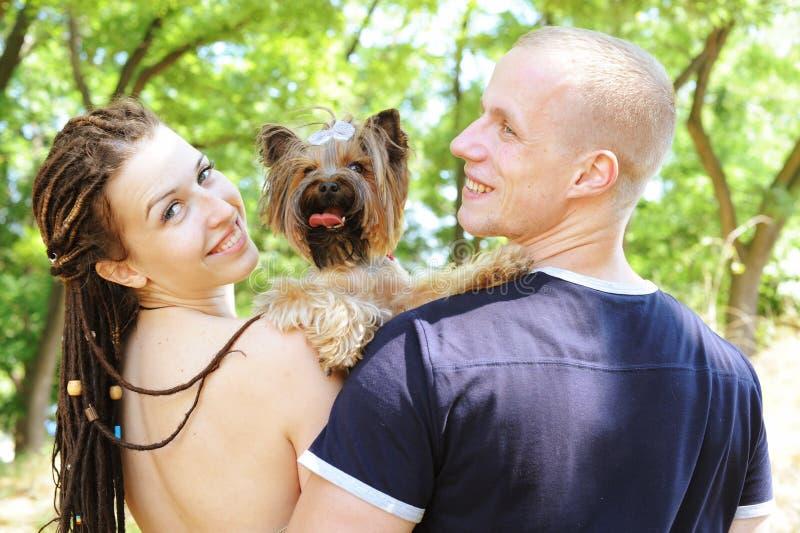 Abraçando pares e seu yorkshire terrier imagens de stock