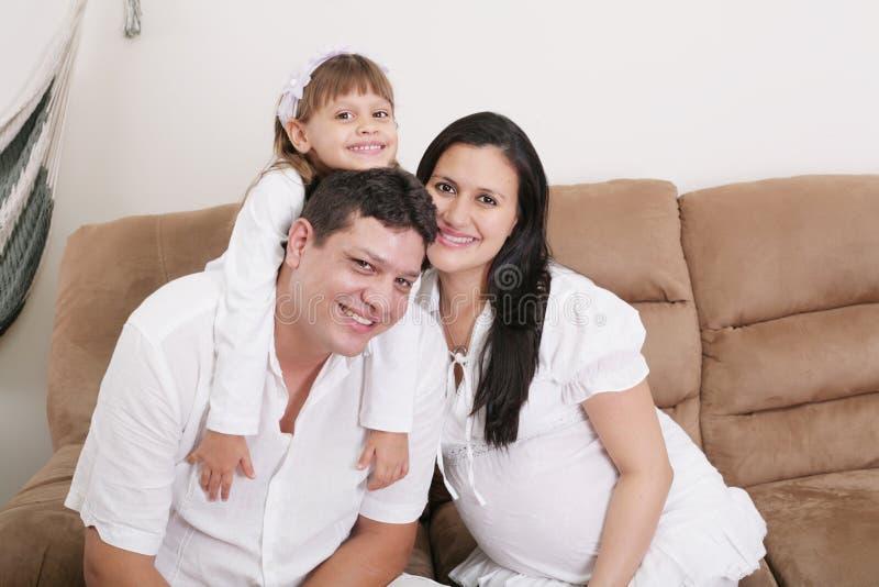 Abraçando uma família feliz com criança em casa e a mãe expectante imagens de stock