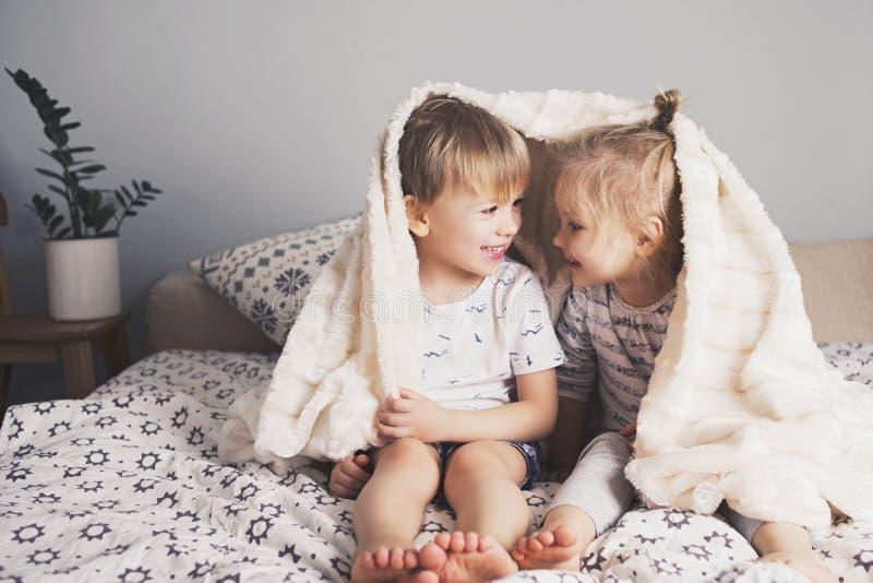 Abraço bonito de duas crianças sob a cobertura fotos de stock royalty free