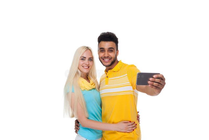 Abraço de sorriso do amor feliz novo bonito dos pares tomando a foto de Selfie no telefone esperto da pilha, mulher latino-americ imagem de stock