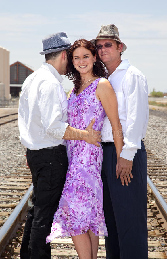 Abraço de uma mulher e de dois homens foto de stock royalty free