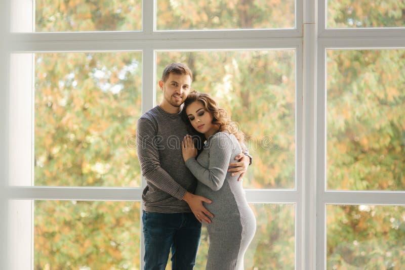 Abraço do homem sua esposa grávida e para pôr sua mão sobre sua barriga Estão perto da janela imagens de stock