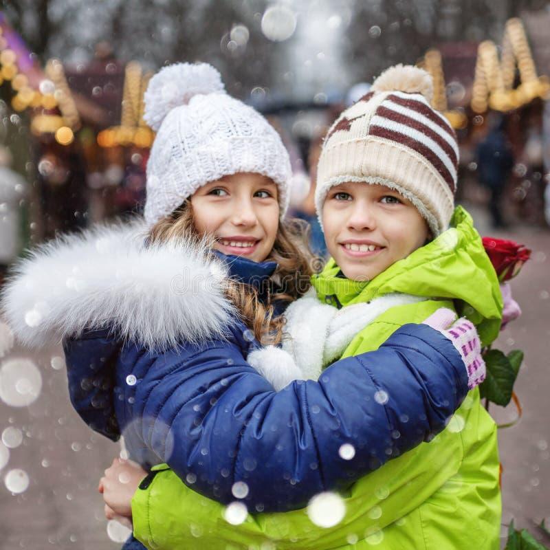 Abraço do rapaz pequeno e da menina na rua quadrado O conceito do estilo de vida, amor, o dia de Valentim imagens de stock