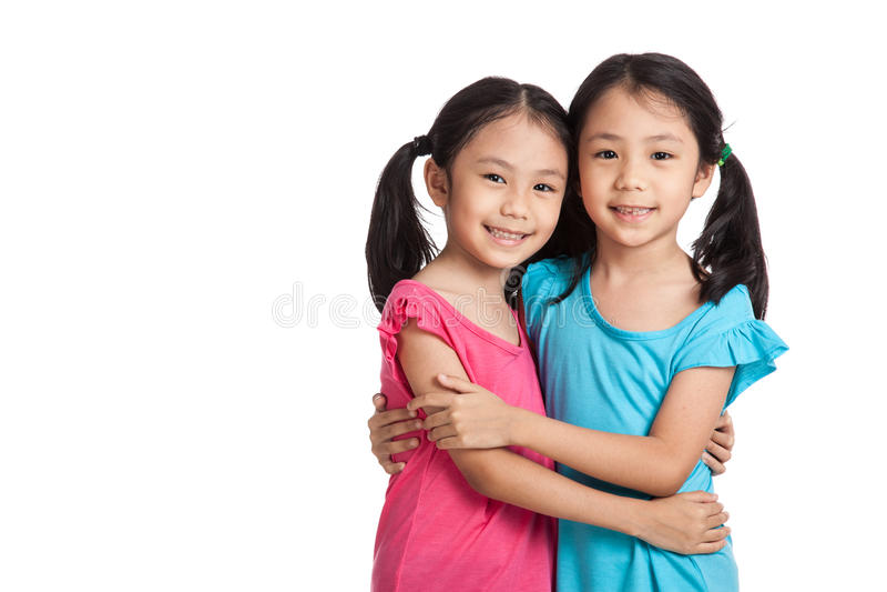 Abraço do sorriso das meninas dos gêmeos do asiático imagem de stock