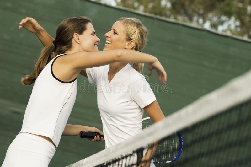Abraço fêmea dos jogadores de ténis imagens de stock royalty free