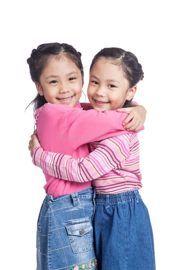 Abraço gêmeo asiático das irmãs com amor imagens de stock royalty free