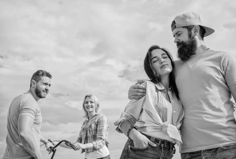 Abraço relaxado do homem e da mulher feliz junto quando o homem no fundo tentar pegarar a amiga nova Relações a longo prazo imagem de stock