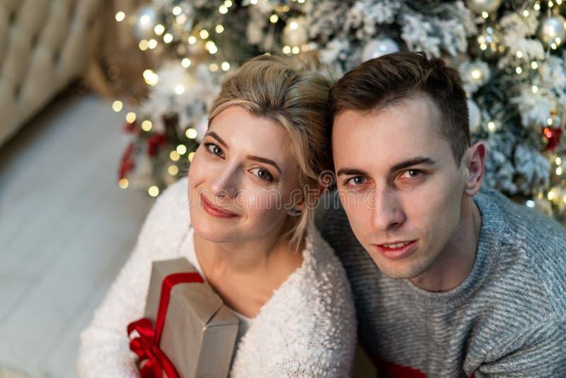 Abraços de amor bonitos dos jovens no fundo da árvore de Natal fotos de stock royalty free