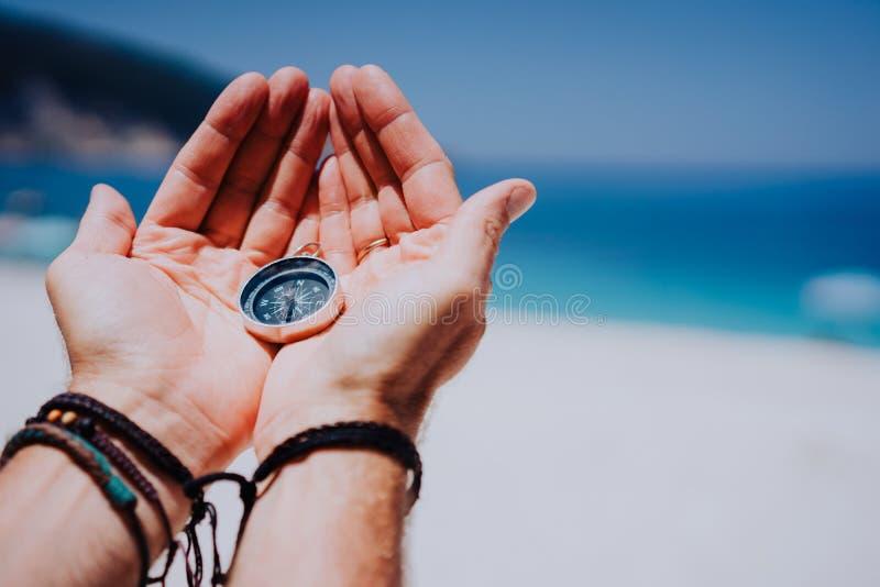 Abra as palmas da mão com compasso do metal no Sandy Beach Procurando seu conceito da maneira Mar azul no fundo Ponto de vista imagem de stock