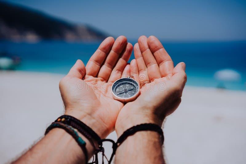 Abra as palmas da mão com compasso do metal no Sandy Beach Procurando seu conceito da maneira Mar azul no fundo Ponto de vista fotografia de stock royalty free