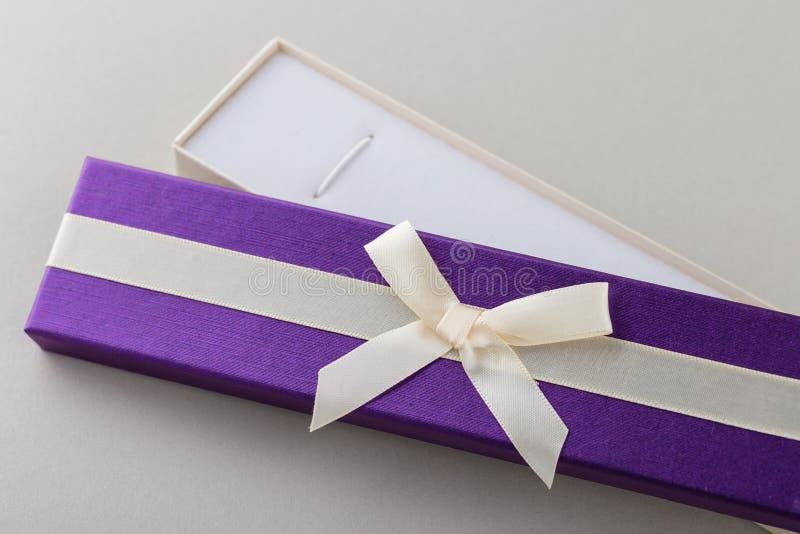 Abra a caixa de presente roxa com curva da fita no fundo cinzento imagens de stock royalty free