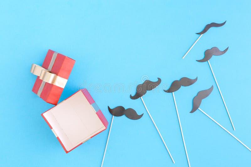 Abra a caixa de presente vermelha com os bigodes de papel no fundo azul imagens de stock