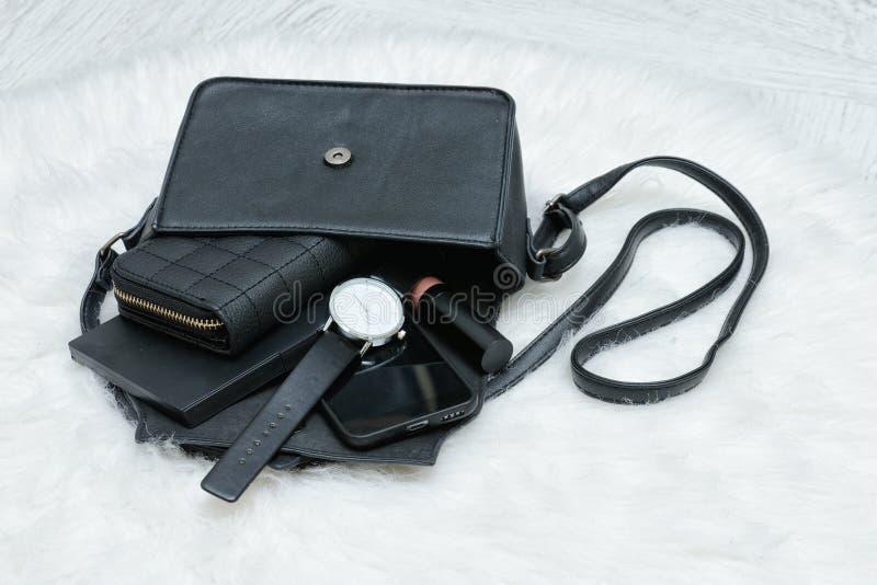 Abra el bolso negro con cosas caídas, cuaderno, teléfono móvil, watc foto de archivo
