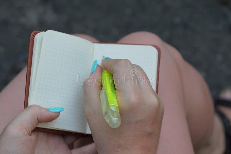 Abra el cuaderno blanco y una pluma verde en las manos de una muchacha sobre sus pies en la calle fotografía de archivo