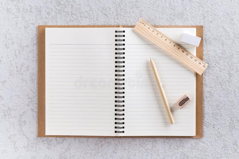 Abra el cuaderno con la pluma, la regla de madera y los sacapuntas de lápiz fotografía de archivo libre de regalías